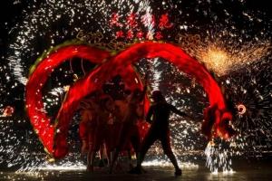 การแสดงเชิดมังกรประกายไฟเหล็กหลอมเหลวในงานวัดฉลองตรุษจีนที่สวนสนุกแฮ็ปปี้ วัลเลย์ กรุงปักกิ่ง เมื่อวันเสาร์ 9 ก.พ. (ภาพ เอพี)