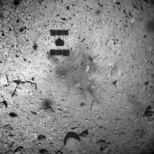 ภาพจากกล้องบนยานฮายาบูซะ 2 ขณะยานอยู่สูงจากพื้นผิวดาวเคราะห์น้อย 30 เมตร โดยเห็นเงาของยานทาบบนพื้นผิวดาวเคราะห์น้อยบริเวณด้านซ้ายบน (Handout / NAGOYA UNIVERSITY / JAXA / TOKYO UNIVERSITY / KOCHI UNIVERSITY / RIKKYO UNIVERSITY / CHIBA INSTITUTE OF TECHNOLOGY / MEIJI UNIVERSITY / AIZU UNIVERSITY / NATIONAL INSTITUTE OF ADVANCED INDUSTRIAL SCIENCE AND TECHNOLOGY / AFP )