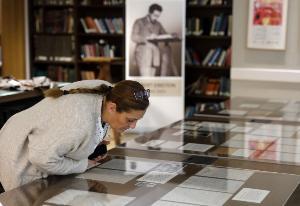ผู้หญิงคนหนึ่งกำลังเพ่งพิจารณาเอกสารลายมือไอน์สไตน์ (MENAHEM KAHANA / AFP)