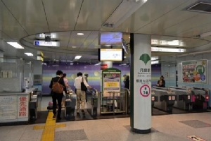 ตัวอย่างทางเข้าออกขึ้นลงรถไฟของ Toei มีโลโก้คล้ายใบพัดสีเขียว  มีสีประจำสายคือสีชมพูวงรอบ E16 บ่งบอกว่าเป็นสาย Toei Oedo  ส่วนเลข 16 คือสถานี Tsukishima