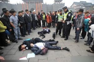 ในเมืองแห่งหนึ่งของจีน ประชาชนและตำรวจกำลังมุงดูกลุ่มชายใส่สูท 3 คนที่ดื่มเยอะจนขาดสตินอนกลางถนน (ที่มา เอเจนซี่)