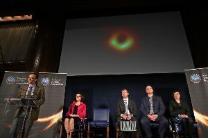 เชเพิร์ด โดเลแมน (Sheperd Doeleman) ผู้อำนวยการเครือข่ายกล้องโทรทรรศน์อีเวนท์ฮอไรซัน เผยภาพแรกของหลุมดำระหว่างแถลงข่าวที่ดำเนินการโดยมูลนิธิวิทยาศาสตร์สหรัฐฯ ณ สโมสรผู้สื่อข่าวสหรัฐฯ ในวอชิงตัน ดีซี (EUROPEAN SOUTHERN OBSERVATORY / AFP )