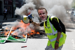 """ผู้ระท้วงคนหนึ่งสวมหน้ากากรูปใบหน้าประธานาธิบดี เอ็มมานูเอล มาครง แห่งฝรั่งเศสที่กำลังร้องไห้ยืนอยู่ข้างๆ รั้วกั้นติดไฟในระหว่างการชุมนุมต่อต้านรัฐบาลที่เรียกกันว่าขบวนการ """"เสื้อกั๊กเหลือง"""" ในกรุงปารีส (20 เม.ษ.)"""