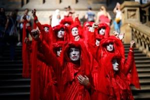 นักเคลื่อนไหวปัญหาสภาพอากาศกลุ่ม Extinction Rebellion ในชุดสีแดงเข้าร่วมการประท้วงแกล้งตายครั้งใหญ่ในหอหลักของพิพิธภัณฑ์ประวัติศาสตร์ธรรมชาติในกรุงลอนดอน (22 เม.ษ.)