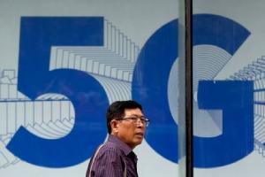 ชายผู้หนึ่งเดินผ่านโฆษณาเครือข่าย 5 จี ซึ่งติดตั้งที่ย่านช็อปปิ้งแห่งหนึ่งในกรุงปักกิ่ง ประเทศจีน เมื่อวันพุธ (15 พ.ค.) ทั้งนี้เห็นกันว่าการที่สหรัฐฯ เล่นงานบริษัทหัวเว่ยนั้น เบื้องลึกเลยคือการมุ่งขัดขวางไม่ให้จีนกลายเป็นเจ้าเทคโนโลยีระบบสื่อสารไร้สายเจเนอเรชันใหม่นี่เอง