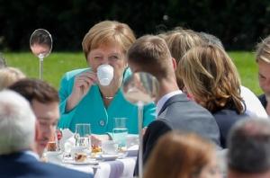 """นายกรัฐมนตรีเยอรมัน อังเกลา แมร์เคิล กำลังจิบกาแฟในงาน """"โต๊ะกาแฟ"""" ที่ถูกจัดขึ้นโดยประธานาธิบดีเยอรมันเพื่อเฉลิมฉลองการครบรอบ 70 ปีของกฎหมายรัฐธรรมนูญเยอรมัน (Grundgesetz)เป็นงานที่ถูกจัดภายในสวนของทำเนียบประธานาธิบดีเยอรมัน กรุงเบอร์ลิน ภาพประจำวันพฤหัสบดี(23) เอเอฟพี"""