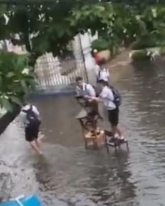 ไม่ยอมเปียก! นักเรียนสุดทุ่มเทนำเก้าอี้ต่อเป็นทางเดิน เหตุถนนน้ำท่วม จากฝนถล่ม (ชมคลิป)