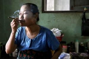 หญิงชาวพม่านั่งสูบเชอรูท หรือซิการ์พม่า ในเมืองพะโค. -- Reuters.
