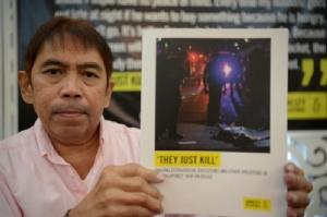บุตช์ โอลาโน ผู้แทนองค์การนิรโทษกรรมสากล (เอไอ) ชูรายงานเกี่ยวกับสงครามยาเสพติดซึ่งใช้ชื่อว่า 'They Just Kill' ขณะเปิดแถลงข่าวที่กรุงมะนิลา วันนี้ (8 ก.ค.)