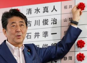 นายกรัฐมนตรี ชินโซ อาเบะ ของญี่ปุ่น ซึ่งเป็นผู้นำของพรรคลิเบอรัล เดโมเครติก ปาร์ตี้ (แอลดีพี) ด้วย ติดดอกกุหลาบไว้ที่ชื่อผู้สมัครของพรรคซึ่งคาดหมายว่าจะชนะการเลือกตั้งสภาสูง ณ สำนักงานใหญ่พรรคแอลดีพี ในกรุงโตเกียว คืนวันอาทิตย์ (21 ก.ค.)