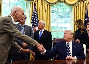 ไมเคิล คอลลินส์ จับมือกับ นาย โดนัลด์ ทรัมป์ ประธานาธิบดีสหรัฐฯ (Brendan Smialowski / AFP)
