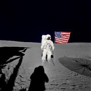เอ็ดการ์ ดี มิทเชล (Edgar D. Mitchell) ลูกเรืออะพอลโล 14 ยืนข้างธงชาติสหรัฐฯ ที่ถูกปักไว้บนดวงจันทร์ ระหว่างภารกิจเดินอวกาศครั้งแรก (HO / NASA / AFP)