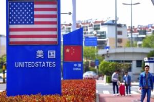 <i>(ภาพจากแฟ้มถ่ายเมื่อ 8 พ.ค. 2019) ผู้คนเดินผ่านแผ่นป้ายที่ติดธงชาติของสหรัฐฯและธงชาติจีน ในพื้นที่เขตการค้าพิเศษ ของเมืองชิงเต่า ทางภาคตะวันออกของจีน  ทั้งนี้คณะผู้เจรจาด้านการค้าของสหรัฐฯและของจีน มีกำหนดเริ่มหารือกันรอบใหม่ ที่เมืองเซี่ยงไฮ้ ในวันอังคาร (30 ก.ค.) และวันพุธ (31) นี้ </i>