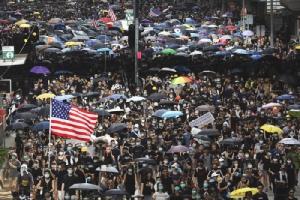 <i>พวกผู้ประท้วงจำนวนหนึ่งถือธงชาติสหรัฐฯและแผ่นป้าย ระหว่างการเดินขบวนในฮ่องกงเมื่อวันอาทิตย์ (28 ก.ค.) ก่อนที่จะเกิดการปะทะกับตำรวจ </i>