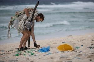 อาสามัครเก็บขยะพลาสติกที่ถูกซัดขึ้นชายหาดบนเกาะแฮนเดอร์สันในมหาสมุทรแปซิฟิกตอนใต้ (Iain McGregor / STUFF / AFP )