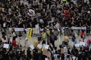 <i>ผู้โดยสารเครื่องบินเดินผ่านผู้ประท้วงจำนวนนับหมื่นซึ่งกำลังนั่งประท้วงอยู่ภายในท่าอากาศยานฮ่องกงเมื่อวันที่ 10 ส.ค.  ทั้งนี้สนามบินฮ่องกงเป็นจุดที่ถูกใช้ในการประท้วงระลอกนี้อยู่หลายครั้ง </i>