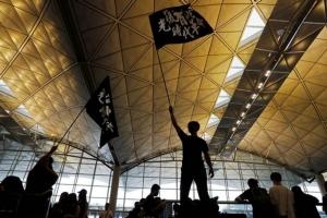 """ผู้ประท้วงชูธง """"อิสรภาพฮ่องกง ปฏิวัติแห่งยุคสมัยของเรา"""" ที่สนามบินนานาชาติฮ่องกง ภาพ 12 ส.ค. (รอยเตอร์ส)"""