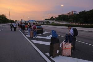 <i>พวกผู้โดยสารพร้อมกระเป๋าเดินทางของพวกเขา ซึ่งติดค้างอยู่บนทางหลวงสายหนึ่งใกล้ๆ ท่าอากาศยานนานาชาติฮ่องกงในวันจันทร์ (12 ส.ค.) ภายหลังทางท่าอากาศยานสั่งยกเลิกเที่ยวบินทั้งหมด เมื่อผู้ประท้วงนับพันนับหมื่นคนเข้าไปนั่งประท้วงในห้องผู้โดยสารขาเข้า </i>