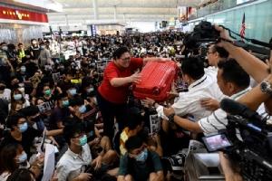 <i>นักท่องเที่ยวผู้หนึ่ง (กลาง) ส่งกระเป๋าเดินทางของเธอให้พวกเจ้าหน้าที่รักษาความปลอดภัย ขณะที่เธอพยายามฝ่ากลุ่มผู้ประท้วงเพื่อผ่านเข้าไปยังประตูขาออก  ของท่าอากาศยานนานาชาติฮ่องกง เมื่อวันอังคาร (13 ส.ค.) </i>