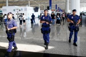 ตำรวจฮ่องกงเดินตรวจตราความสงบเรียบร้อยภายในอาคารผู้โดยสารขาออกของสนามบินนานาชาติฮ่องกง วันนี้ (14 ส.ค.)