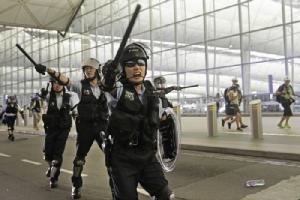 <i>ตำรวจปราบจลาจลวิ่งกรูและตะโกนใส่กลุ่มผู้ประท้วง ระหว่างการชุมนุมประท้วงในท่าอากาศยานนานาชาติฮ่องกงเมื่อคืนวันอังคาร (13 ส.ค.) </i>