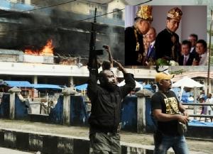 ตำรวจอินโดนีเซียยกปืนไรเฟิลขึ้นฟ้าระหว่างตลาดเมืองฟากฟาก จังหวัดปาปัวตะวันตกกำลังถูกไฟไหม้ในวันพุธ(21)