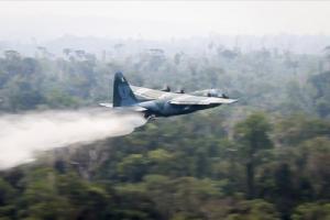 """<i>ภาพที่เผยแพร่โดยกระทรวงกลาโหมบราซิล  แสดงให้เห็นเครื่องบินบรรทุกแบบ ซี 130 """"เฮอร์คิวลิส"""" กำลังปล่อยน้ำลงไปเพื่อดับไฟป่า เมื่อวันเสาร์ (24 ส.ค.) </i>"""