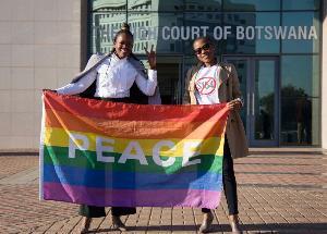 นักรณรงค์ถือธงสายรุ้งหน้าศาลสูงในบอตสวานา เพื่อเรียกร้องให้ลดโทษแก่กลุ่มรักร่วมโทษเมื่อเดือน มิ.ย.ที่ผ่านมา (Tshekiso Tebalo / AF)