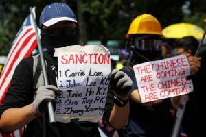 ผู้ประท้วงถือป้ายฯ ระหว่างการชุมนุมบริเวณย่านเซนทรัล ฮ่องกงเมื่อวันอาทิตย์ที่ 8 ก.ย. (ภาพ รอยเตอร์ส)