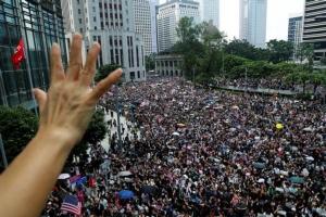 ผู้ประท้วงชูห้านิ้วขณะมาชุมนุมประท้วงที่สถานกงสุลอเมริกาในฮ่องกง ในวันอาทิตย์(8 ก.ย.) (ภาพ รอยเตอร์ส)