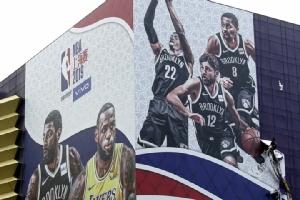 เมื่อวันพุธ (9 ต.ค.) คนงาน (ขวาล่างของภาพ) รื้อถอนบิลบอร์ดโฆษณาเกมแข่งขันบาสเกตบอลพรีซีซั่นของ NBA ที่เดิมกำหนดจัดขึ้นในเมืองเซี่ยงไฮ้ ประเทศจีน ในวันพฤหัสบดี (10)  ทั้งนี้NBA ประกาศระงับกิจกรรมในแดนมังกรไปหลายอย่าง รวมทั้งยังไม่ชัดเจนว่าพวกทีม NBA จะแข่งขันในจีนสัปดาห์นี้ตามกำหนดหรือไม่