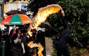 <i>พวกผู้ประท้วงต่อต้านรัฐบาล ขว้างระเบิดขวดน้ำมันใส่สถานีตำรวจจิมซาจุ่ย  ระหว่างการประท้วงที่ฮ่องกงวันอาทิตย์ (20 ต.ค.) </i>