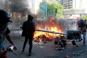 ผู้ชุมนุมจุดไฟเผาสัญญาณไฟจราจรระหว่างการประท้วงต่อต้านรัฐบาลชิลีในกรุงซันติอาโก เมื่อวันอังคาร(29ต.ค.)