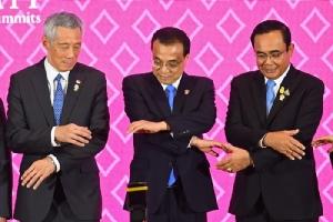 <i>นายกรัฐมนตรีหลี่ เค่อเฉียง ของจีน (กลาง) พยายามคล้องแขนจับมือกับนายกรัฐมนตรีลี เซียนลุง ของสิงคโปร์ และนายกรัฐมนตรี พล.อ.ประยุทธ์ จันทร์โอชา เพื่อถ่ายภาพหมู่ ระหว่างการประชุมสุดยอดจีน-อาเซียน เมื่อวันอาทิตย์ (3 พ.ย.) </i>