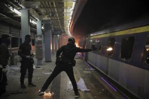 """<i>นักศึกษาสวมหน้ากากผู้หนึ่งขว้างระเบิดขวดน้ำมันเข้าไปภายในขบวนรถไฟ ซึ่งจอดอยู่ภายในสถานีรถไฟใต้ดิน """"ไชนีส ยูนิเวอร์ซิตี้""""  ในฮ่องกงเมื่อวันพุธ (13 พ.ย.)  มหาวิทยาลัยชื่อดังของฮ่องกงแห่งนี้เป็นจุดหนึ่งซึ่งพวกผู้ประท้วงปะทะรุนแรงกับตำรวจมาตั้งแต่วันอังคาร (12) <i>"""