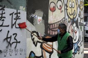 คนงานทำความสะอาดกำแพงด้านนอกอาคารแห่งหนึ่งในฮ่องกงที่ถูกพวกผู้ประท้วงเขียนข้อความเปรอะเปื้อน เมื่อวันจันทร์ (9 ธ.ค.) ทั้งนี้ตำรวจฮ่องกงแถลงว่า การชุมนุมเดินขบวนครั้งใหญ่ในวันอาทิตย์ (8) ส่วนใหญ่เป็นไปด้วยความสงบ แต่ก็มีผู้ก่อจลาจลส่วนน้อยทำลายทรัพย์สร้างความเสียหายให้แก่สถานที่ราชการและทรัพย์สินของเอกชนหลายราย