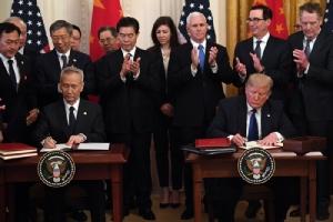 <i>ประธานาธิบดีโดนัลด์ ทรัมป์ ของสหรัฐฯ (ขวา) และ รองนายกรัฐมนตรี หลิว เหอ ของจีน (ซ้าย) ลงนามในข้อตกลงการค้า เฟส 1 ในพิธีซึ่งจัดขึ้นที่ห้องอีสต์รูม ของทำเนียบขาว ในกรุงวอชิงตัน เมื่อวันพุธที่ 15 ม.ค. </i>