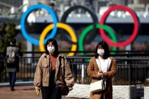 """ผู้คนสวมหน้ากากอนามัยเดินอยู่หน้าวงกลม 5 วงสัญลักษณ์กีฬาโอลิมปิก ในกรุงโตเกียว   ทั้งนี้ไวรัส """"โควิด-19"""" ที่ทำท่าระบาดรุนแรงขึ้นในญี่ปุ่น กำลังทำให้เกิดคำถามว่ามหกรรมกีฬาโอลิมปิกโตเกียว 2020 จะยังสามารถจัดขึ้นตามกำหนดเดิมได้หรือไม่"""