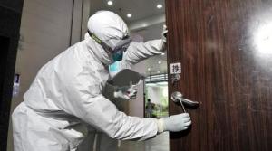 เจ้าหน้าที่กำลังเก็บตัวอย่างเชื้อไวรัสที่อาจปนเปื้อนบนลูกบิดประตู (เครดิตภาพ Guangzhou News)