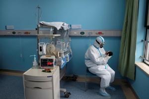 พยาบาลจีนที่สวมชุดป้องกัน กำลังดูแลเด็กทารกที่ติดเชื้อไวรัสโควิด-19