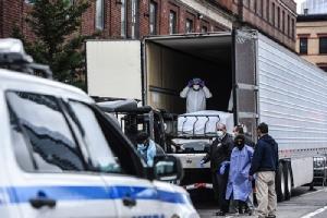 บุคลากรสาธารณสุขกำลังนำศพผู้เสียชีวิตจากโควิด-19ออกจากรถบรรทุกห้องเย็นหน้า รพ.บรูคลิน มหานครนิวยอร์ก วานนี้ (31 มี.ค.) โดย รพ.ต้องใช้รถบรรทุกห้องเย็นเป็นที่เก็บศพ เนื่องจากจำนวนผู้เสียชีวิตจากโควิด-19 ในสหรัฐฯ เพิ่มสูงขึ้นอย่างมาก (ภาพเอเอฟพี)