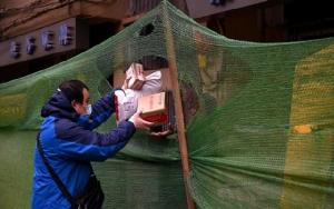 คนงานสวมหนน้ากากยื่นพัสดุให้กับชาวบ้านในเมืองอู่ฮั่น ในมณฑลหูเป่ยของจีน เมื่อวันที่ 30 มีนาคม