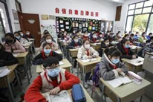 นักเรียนโรงเรียนประถมแห่งหนึ่ง ในเมืองฮว่ายอาน มณฑลเจียงซู ทางภาคตะวันออกของจีน สวมหน้ากากอนามัยเข้าห้องเรียนในวันอังคาร (7 เม.ย.) ภายหลังโรงเรียนเปิดเทอมอีกครั้ง เมื่อการระบาดของไวรัสโควิด-19 สร่างซาลง