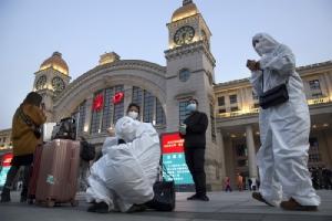 <i>ผู้โดยสารที่ยังคงสวมชุดป้องกันโรค รวมตัวกันอยู่ด้านนอกของสถานีรถไฟฮั่นโข่ว  ในเมืองอู่ฮั่น เมืองเอกของมณฑลหูเป่ยทางภาคกลางของจีน ตอนเช้ามืดวันพุธ (8 เม.ย.) ก่อนหน้าเวลาให้บริการรถไฟไปยังเมืองต่างๆ ทั่วแดนมังกรเริ่มต้นขึ้นมาอีกครั้ง </i>