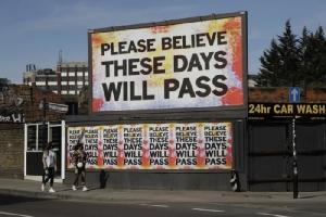 "<i>ป้ายบิลบอร์ดที่เป็น ผลงานของศิลปิน มาร์ก ทิตชเนอร์ ตั้งเด่นอยู่ในย่านตะวันออกของลอนดอน, สหราชอาณาจักร เมื่อวันอังคาร (7 เม.ย.) สำหรับตัวหนังสือในป้ายเขียนว่า ""โปรดเชื่อเถิด วันเวลาเหล่านี้จะต้องผ่านพ้นไป"" </i>"
