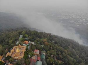 ภาพควันจากไฟป่ารุกโชนที่อยู่ใกล้กับวัดพระธาตุดอยสุเทพ (ภาพ : ทีมโดรนอาสา)