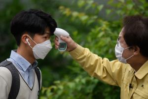 นักเรียนเกาหลีใต้สวมหน้ากากอนามัยและรับการตรวจวัดอุณหภูมิร่างกายโดยเจ้าหน้าที่ฝ่ายการศึกษา ขณะเดินทางไปถึงโรงเรียนมัธยมคยุงบ็อกในกรุงโซล เช้าวันนี้ (20 พ.ค.)