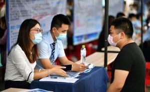 นายจ้าง (ซ้าย) พูดคุยกับผู้สมัครในงานจัดหางานที่เมืองไห่โข่ว มณฑลไห่หนาน ทางตอนใต้ของจีน (แฟ้มภาพซินหัว ถ่ายเมื่อวันที่ 18 เม.ย.2020)