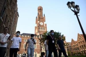 พนักงานของหัวเว่ย เดินไปตามถนนในบริเวณซึ่งก่อสร้างตกแต่งแบบธีมยุโรป ในเขตเมืองตงกวน