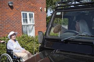 """จูดี้ จิลลิงแฮม (ขวา นั่งอยู่ในรถ) อวดสุนัขของเธอกับ โดโรธี แซกซ์บี ผู้เป็นเพื่อนของเธอ (ซ้าย) ระหว่างการเยี่ยมเยียนด้วยการขับรถผ่าน ณ บ้านพักผู้สูงอายุ """"เกรซเวลล์"""" ใกล้ๆ บานบิวรี ทางตะวันตกของกรุงลอนดอน เมื่อวันพฤหัสบดี (28 พ.ค.) ทั้งนี้ทางการเพิ่งผ่อนปรนให้ไปเยี่ยมผู้สูงอายุซึ่งพำนักอยู่ที่ """"เกรซเวลล์"""" ได้เป็นครั้งแรกตั้งแต่เริ่มล็อกดาวน์เพื่อสกัดโรคระบาดโควิด-19 เมื่อต้นเดือนมี.ค."""
